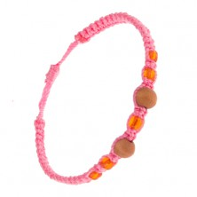 Pleciona różowa bransoletka, pomarańczowe koraliki i kulki z drewna