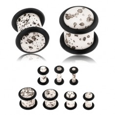 Akrylowy plug do ucha, powierzchnia białego koloru z czarnymi plamkami, czarne gumeczki