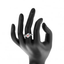 Błyszczący pierścionek w srebrnym odcieniu, splecione ramiona, okrągła czerwona cyrkonia