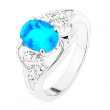 Pierścionek srebrnego koloru, duża niebieska owalna cyrkonia, asymetryczne linie