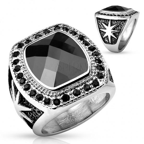 Masywny stalowy pierścionek srebrnego koloru, duży czarny kamień i okrągłe cyrkonie