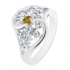 Lśniący pierścionek o falistych ramionach srebrnego koloru, bezbarwne i zielone cyrkonie