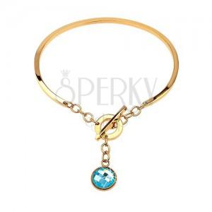 Stalowa bransoletka złotego koloru, niepełny owal z wiszącą niebieską cyrkonią