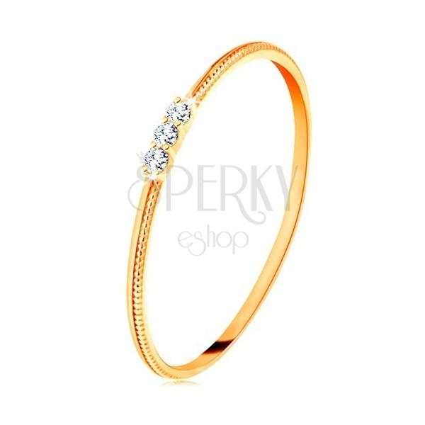 Pierścionek z żółtego 9K złota - cienkie ramiona z nacięciami, trzy bezbarwne cyrkonie